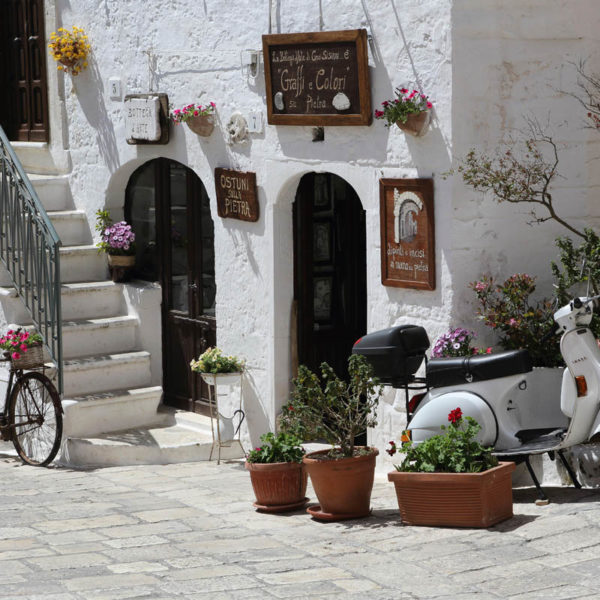 A bicycle, scooter and flower boxes by a shop in Ostuni in Italy. Ostuni is known as the 'white city' (Citta Bianca).