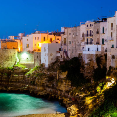 Polignano a Mare at night. Sea and rocks. The old town above the sea