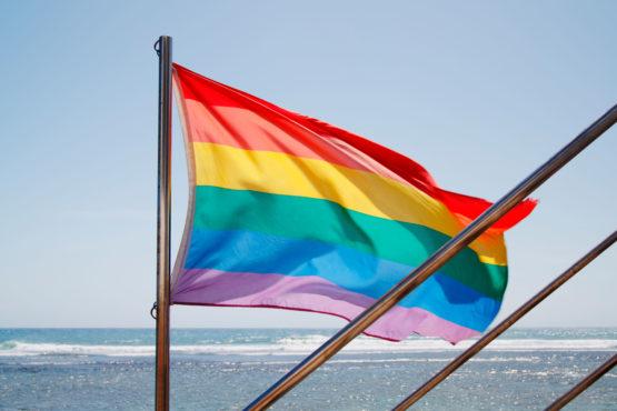C1YFGC Rainbow flag outside bar on Maspalomas beach on Gran Canaria, Canary Islands