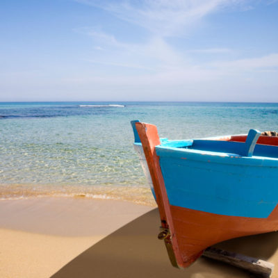 Blue painted rowing boat on beach near Gallipoli, Southern Italy